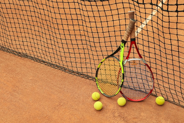 Rackets and tennis balls against net on clay court