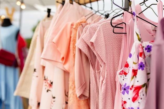 Стойки с одеждой на открытом воздухе.ер продает одежду на городской ярмарке