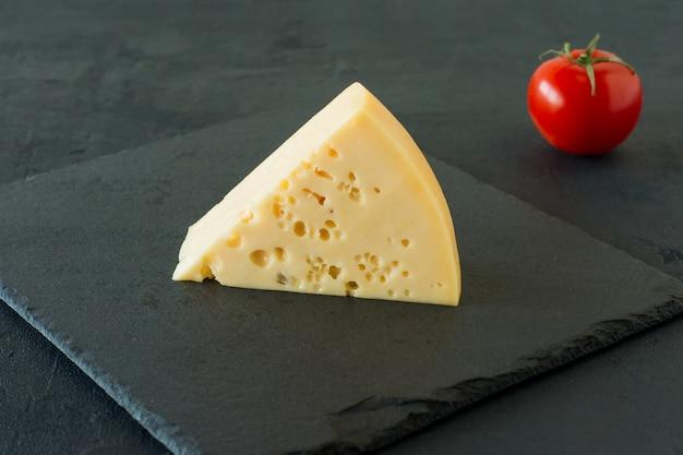 Сыр радамер на черном фоне бетона. треугольный кусок желтого швейцарского сыра из коровьего молока с отверстиями.