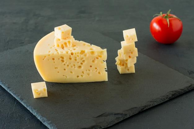 黒のコンクリートの背景にラダマーチーズ。穴の開いた黄色い牛のミルクスイスチーズの三角形の部分。