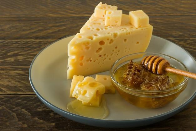 はちみつを添えた皿の上のラダマーチーズ。穴の開いた黄色い牛のミルクスイスチーズの三角形の部分。