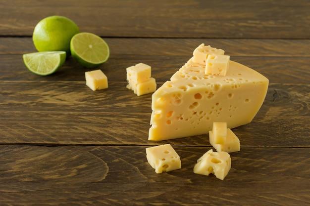 木の板にライムを添えたラダマーチーズ。穴の開いた黄色い牛のミルクスイスチーズの三角形の部分。