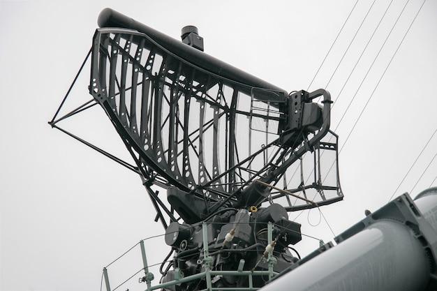 多くのケーブルと金属部品を備えた灰色の空に対する軍艦のレーダーシステム