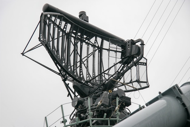 Radar system on warship against gray sky with a lot of cables and metal parts