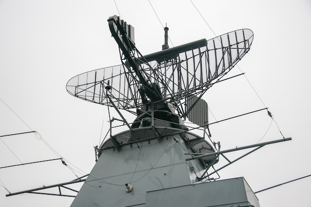 Radar on a warship on a metal structure against a gray sky. a lot of wires and metal parts. rainy gloomy weather.