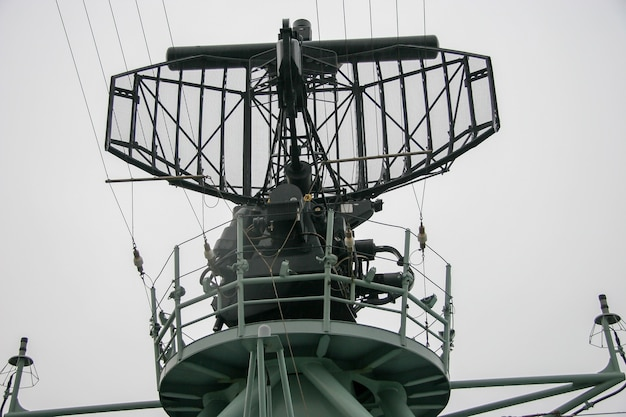 Radar on a warship with a circular platform for people. a lot of wires and parts. rainy gloomy weather.