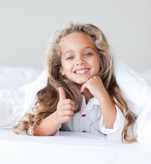 Radiant little girl in a white bed