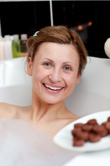 Radiant woman eating chocolate while having a bath