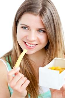 Сияющая молодая женщина, питающаяся картофелем фри