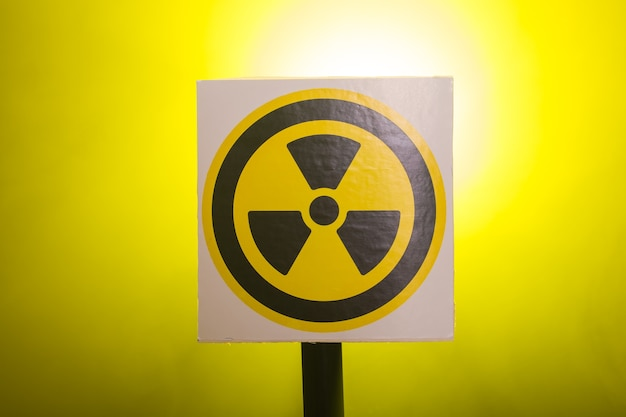 Radiation and danger concept - radioactivity sign and the dramatic smokey background.