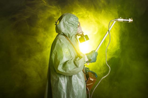 방사선, 오염 및 위험 개념-보호 복 남자와 어두운 배경에 가스 마스크