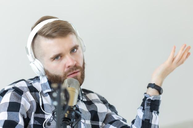 라디오 및 dj 개념-마이크와 큰 헤드폰을 가진 남자가 작동합니다.