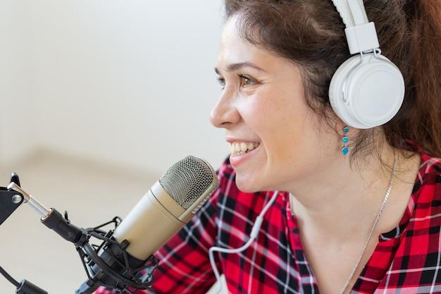 Radio, blogging, podcasting concept - close-up woman presenter on the radio