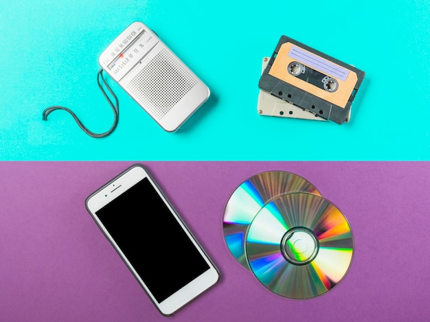 Radio; cassette; cd and cell phone on dual colored backdrop