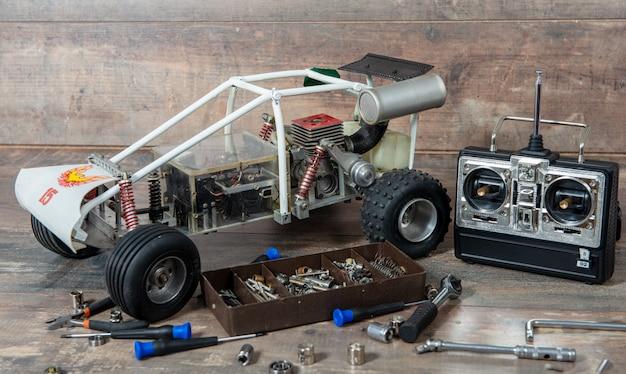 Радиоуправляемая модель автомобиля с инструментами для ремонта радиоуправляемых моделей и пультом управления.