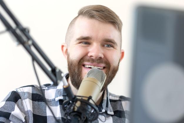 Концепция радио, диджея и трансляции - портрет красивого молодого человека со светлыми волосами, ведущего шоу в прямом эфире