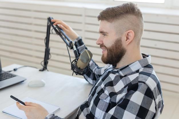 라디오, dj, 블로거 및 사람들 개념 - 라디오 스튜디오에서 작업하고 마이크에 대해 이야기하는 젊은 남자 발표자