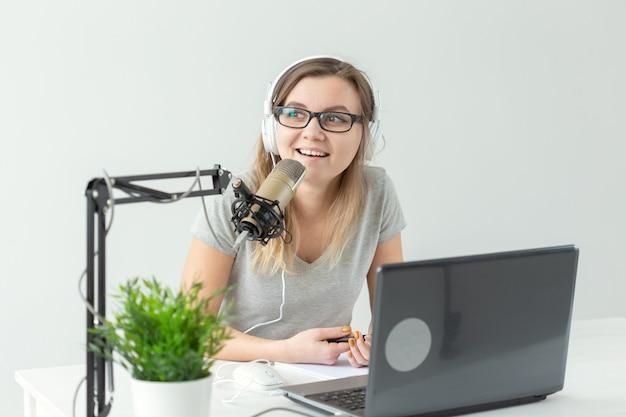 Концепция радио, диджея, блоггера и людей - ведущая молодая женщина, работающая на радиостудии и