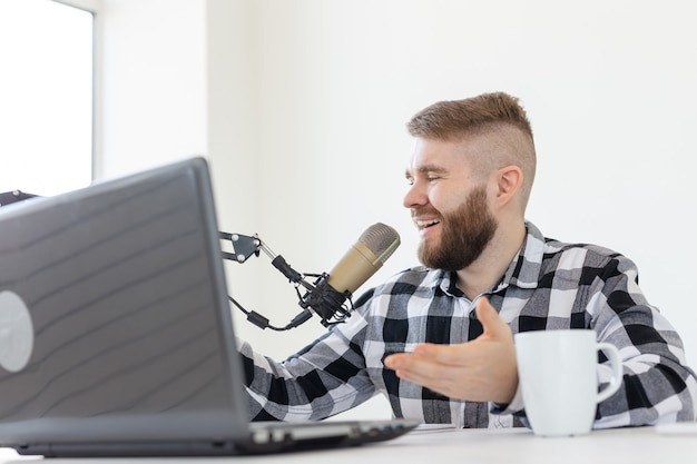 Radio, dj, blogging and people concept - smiling man sitting in front of microphone, host at radio