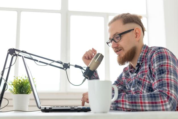 ラジオホストの概念-ラジオ局でラジオホストとして働いているハンサムな男性のクローズアップ