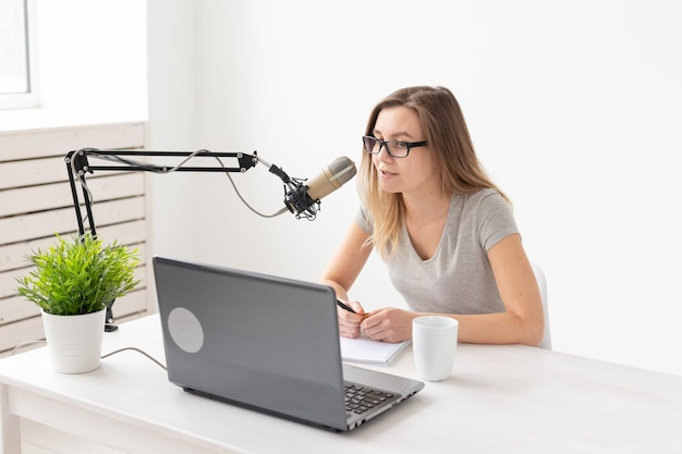 ラジオホストの概念-ラジオ局でラジオホストとして働いている若い女性