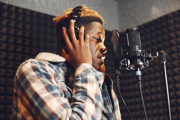 ラジオスタジオでポッドキャストを録音しながら身振りで示すラジオホスト。アフリカ人男性がレコーディングスタジオでリハーサルをします。