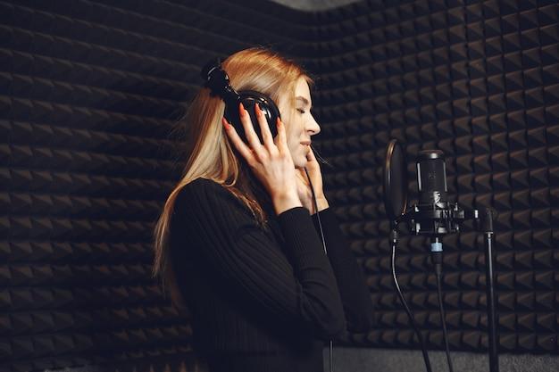 ラジオスタジオでポッドキャストを録音しながら身振りで示すラジオホスト。