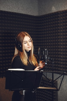 Radio host gesturing while recording podcast in radio studio.