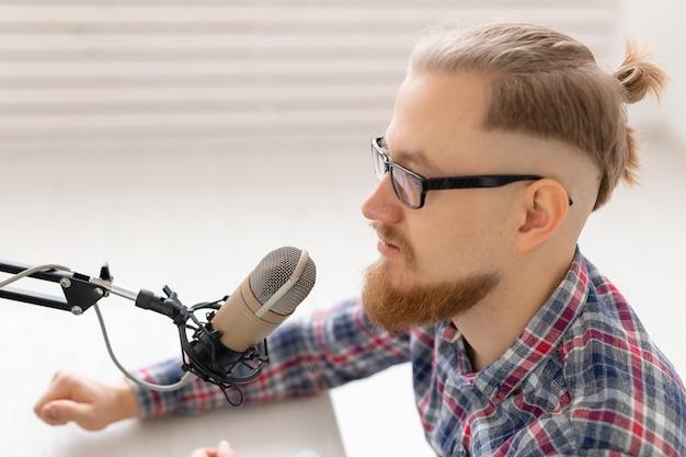 ラジオホスト、ストリーマー、ブロガーのコンセプト-マイクの前に座っているラジオ局でラジオホストとして働いているハンサムな男性のクローズアップ