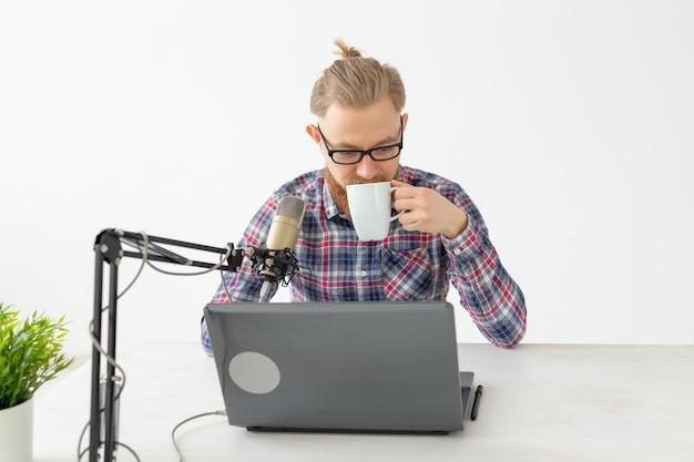ラジオホスト、ストリーマー、ブロガーのコンセプト-マイクの前に座っているラジオ局でラジオホストとして働いているハンサムな男