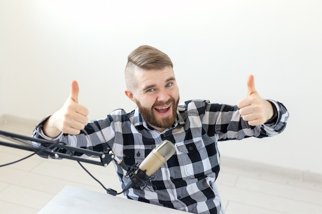 Radio host streamer and blogger concept - man gesturing thum up over white background, host at radio
