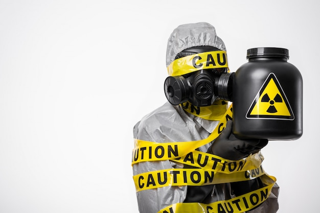 Radioactive contamination. a scientist chemist in a protective suit, wrapped in a yellow tape