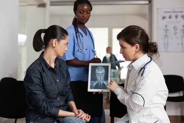 病気の女性患者に臨床的回復を説明する放射線科医