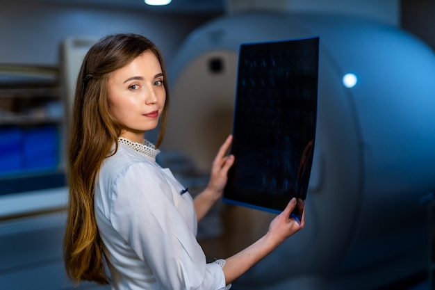 Radiologist female doctor with x-ray picture in hands. ct machine on background.