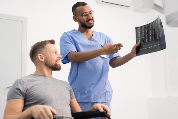 クリニックでそれを指さしながら彼の壊れた関節の車椅子のx線で患者を示す青い制服を着た放射線科医