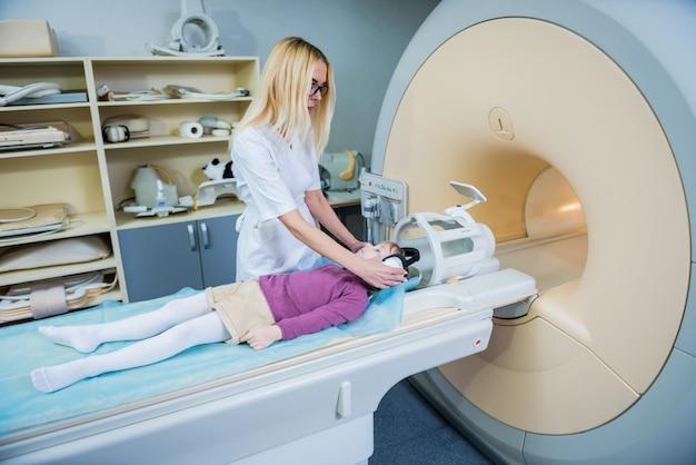 Radiologist prepares the little girl for an mri brain examination