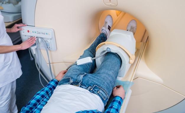 방사선과 의사가 환자에게 mri 무릎 검사를 준비합니다.