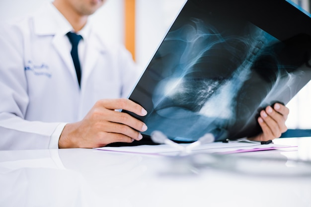 Radiology doctor examining at chest x ray film of patient at health care clinic