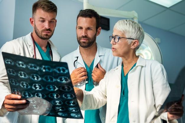 Радиология, здравоохранение, люди, концепция хирургии и медицины. группа врачей, глядя на изображение рентгеновского снимка
