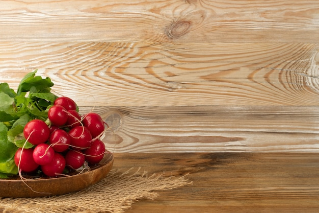 Radis bunch on wooden table with copy space. fresh radish root bundle on wood plate, pile of red radishes with green leaves