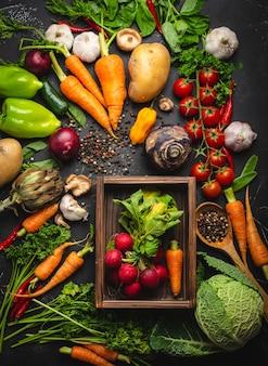 素朴な黒いコンクリートの背景に古い木製の箱と新鮮な農場の有機野菜の大根とニンジンの新鮮な束。秋の収穫、ベジタリアン料理または清潔で健康的な食事の概念、上面図