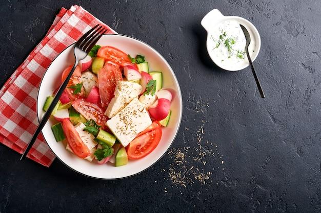 블랙 슬레이트, 돌 또는 콘크리트 배경에 흰색 그릇에 향신료 후추와 올리브 오일을 곁들인 무, 오이, 토마토, 후추, 페타 치즈. 건강 식품 개념입니다. 평면도.