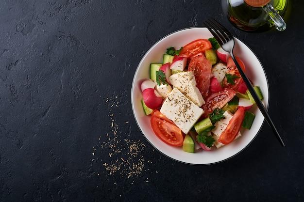 大根、きゅうり、トマト、コショウ、フェタチーズとスパイスペッパーとオリーブオイルを白いボウルに入れ、黒いスレート、石、またはコンクリートの背景に。健康食品のコンセプト。上面図。