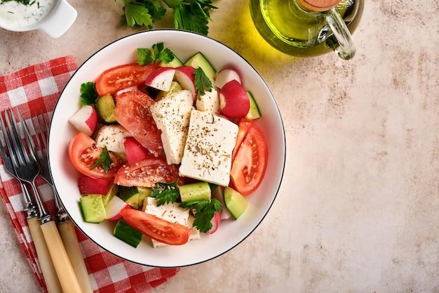 회색 슬레이트, 돌 또는 콘크리트 배경에 흰색 그릇에 향신료 후추와 올리브 오일을 넣은 무, 오이, 토마토, 후추, 페타 치즈. 건강 식품 개념입니다. 평면도.