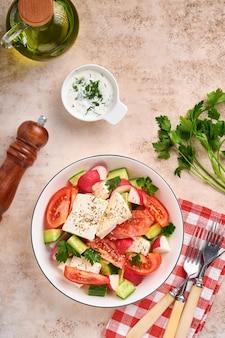 大根、きゅうり、トマト、コショウ、フェタチーズとスパイスペッパーとオリーブオイルを灰色のスレート、石、またはコンクリートの背景に白いボウルに入れます。健康食品のコンセプト。上面図。