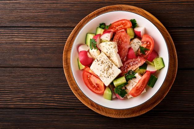 무, 오이, 토마토, 후추, 페타 치즈와 향신료 후추, 올리브 오일이 오래된 나무 어두운 테이블 배경에 있는 흰색 그릇에 있습니다. 건강 식품 개념입니다. 평면도.