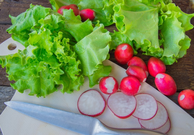 Radishes and fresh organic lettuce on a dark wooden background
