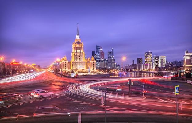 모스크바의 radisson hotel은 저녁 조명과 도시 고속도로의 자동차 헤드 라이트 흔적에 있습니다.