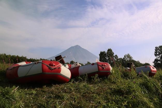 Klyuchevskaya sopka 화산 배경에 푸른 잔디가 있는 개간지에 래프팅 보트가 주차되어 있습니다. 배경 풍경에 klyuchevskoy 화산입니다. 러시아 극동 캄차카의 실제 모험. 저작권