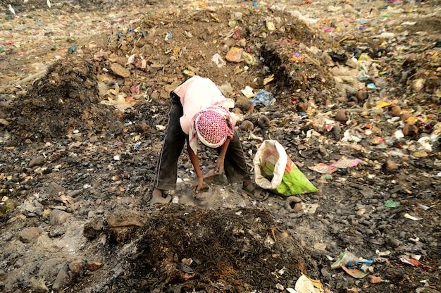 Rag pickers는 인도의 쓰레기 토지와 대기 오염에서 재활용 가능한 물질을 검색합니다.